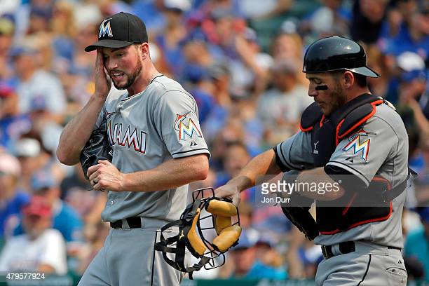 Carter Capps of the Miami Marlins and Jeff Mathis walk to the pitchers mound during the ninth inning against the Chicago Cubs at Wrigley Field on...
