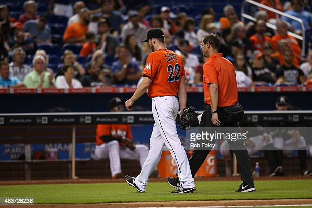 Carter Capps of the Miami Marlins walks off the field with a trainer during the game against the San Diego Padres at Marlins Park on August 2 2015 in...