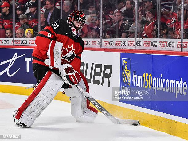 Carter Hart of Team Canada looks to play the puck along the boards during the 2017 IIHF World Junior Championship semifinal game against Team Sweden...