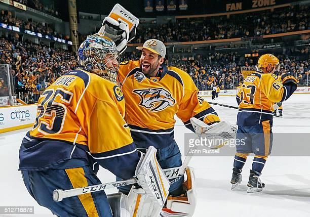 Carter Hutton congratulates Pekka Rinne of the Nashville Predators on his shutout win against the St Louis Blues during an NHL game at Bridgestone...