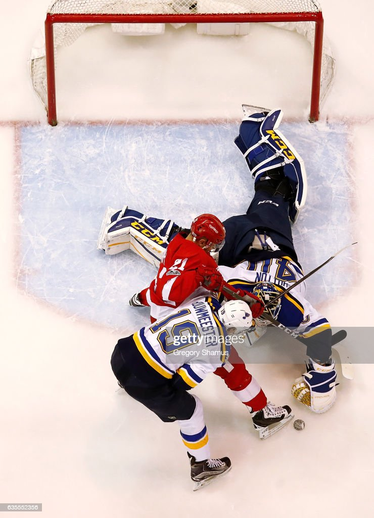 Carter Hutton #40 of the St. Louis Blues dives for the puck next to Tomas Tatar #21 of the Detroit Red Wings and teammate Scottie Upshall #10 at Joe Louis Arena on February 15, 2017 in Detroit, Michigan. St. Louis won the game 2-0.