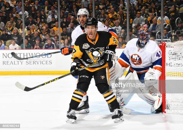 Carter Rowney of the Pittsburgh Penguins battles for position in front of Travis Hamonic and Jaroslav Halak of the New York Islanders at PPG Paints...