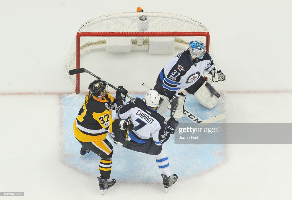 Carter Rowney #37 of the Pittsburgh Penguins battles for position with Ben Chiarot #7 of the Winnipeg Jets in front of Connor Hellebuyck #37 in the first period during the game at PPG PAINTS Arena on February 16, 2017 in Pittsburgh, Pennsylvania.