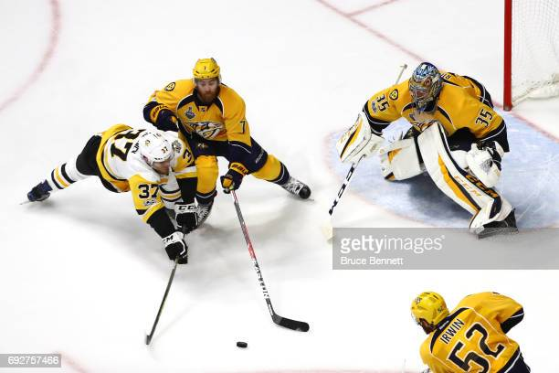 Carter Rowney of the Pittsburgh Penguins is defended by Yannick Weber as Pekka Rinne of the Nashville Predators tends to net during the second period...