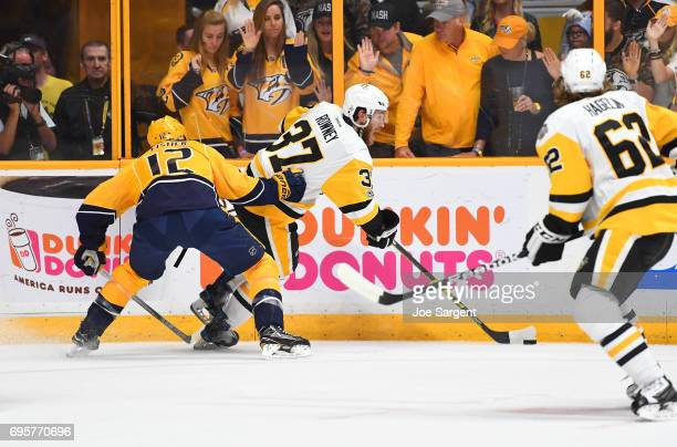 Carter Rowney of the Pittsburgh Penguins plays the puck away from Mike Fisher of the Nashville Predators in the first period of Game Six of the 2017...