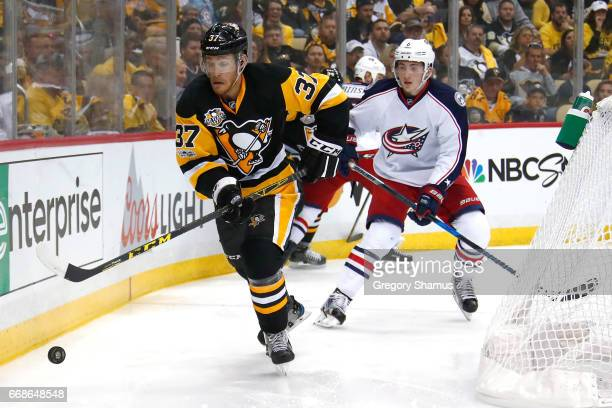 Carter Rowney of the Pittsburgh Penguins tires to control the puck in front of Zach Werenski of the Columbus Blue Jackets during the second period in...
