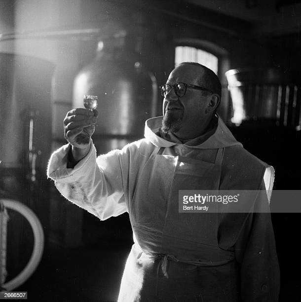 A Carthusian monk with a glass of Chartreuse liqueur in the distillery at the Monastery of the Grande Chartreuse in Dauphine southeastern France...
