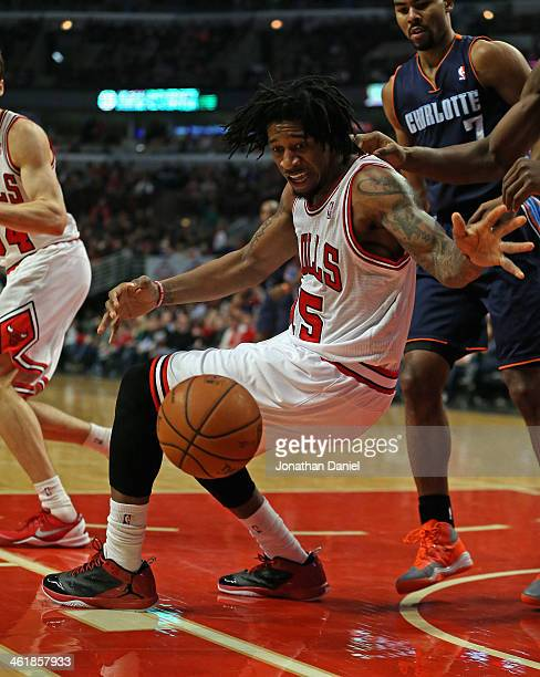 Cartier Martin of the Chicago Bulls tries to collect a loose ball against the Charlotte Bobcats at the United Center on January 11 2014 in Chicago...