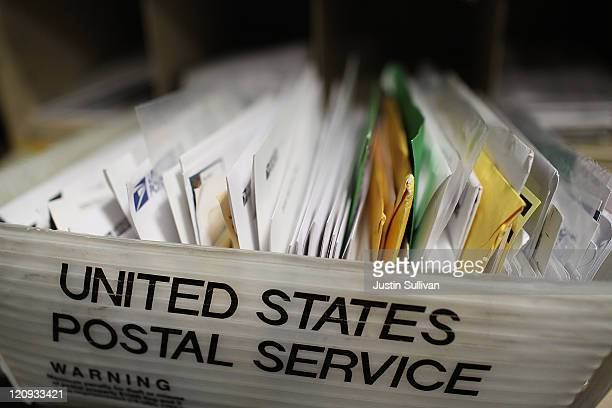 Cartons of mail ready to be sorted sit on a shelf at the US Post Office sort center on August 12 2011 in San Francisco California The US Postal...