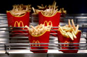 Cartons of McDonald's french fries sit at a restaurant in London UK on Monday Feb 1 2010 McDonald's Corp the world's largest restaurant company plans...