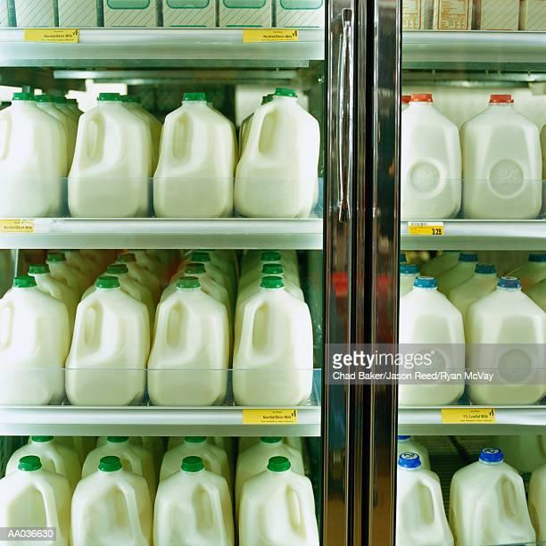 Cartons of milk in supermarket refrigerator, full frame