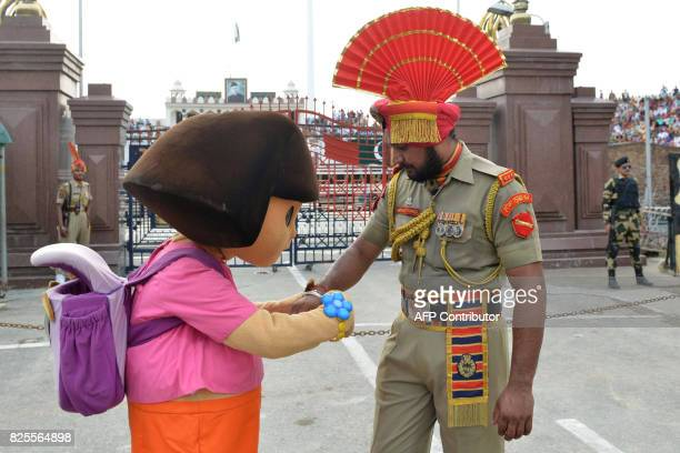 Cartoon character Dora the Explorer ties 'Rakhi' sacred thread onto the wrist of an Indian Border Security Force personnel during celebrations before...