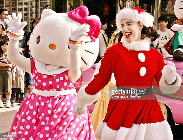 Cartoon character Hello Kitty and a woman dressed as Santa perform rock'n'roll dance on the street at the Universal Staudios Japan in Osaka western...