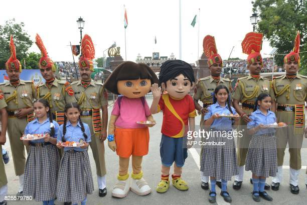 Cartoon characters Dora the Explorer Shiva pose after tying 'Rakhi' sacred thread onto the wrist of an Indian Border Security Force personnel during...