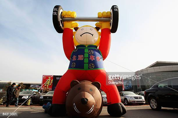 A cartoon model is installed in front of an auto market on January 16 2009 in Beijing China The Chinese government has announced a rescue package for...