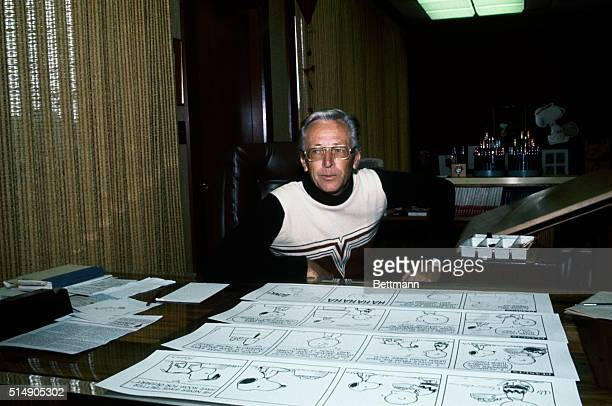 3/1/1978 Cartoonist Charles Schulz creator of the strip 'Peanuts' shown at desk with sketches for cartoon