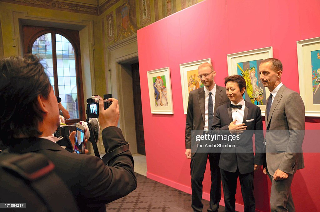 Cartoonist Hirohiko Araki (C) and Gucci staffs pose for photographs at his origianal drawing exhibition opening on June 27, 2013 in Florence, Italy.