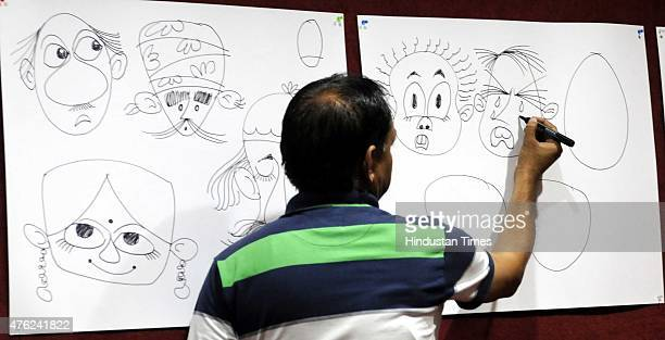 Cartoonist Ismail Lahari imparted drawing tips during a cartoon drawing workshop organised by Indore Press Club on June 7 2015 in Indore India