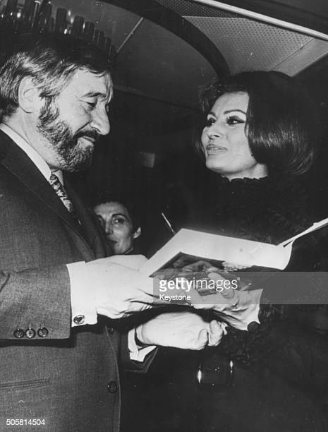 Cartoonist Raymond Peynet talking to actress Sophia Loren over a copy of her book 'Cookingwith Love' which he illustrated for her aboard the boat...