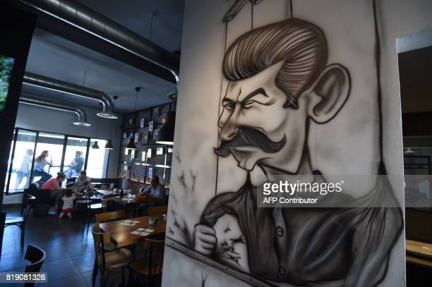 Cartoons adorn the walls of restaurant 'The Dictator' on July 5 2017 in the upmarket Cite Ennasr suburb of Tunis A steak named 'Grilled Freedom' is...