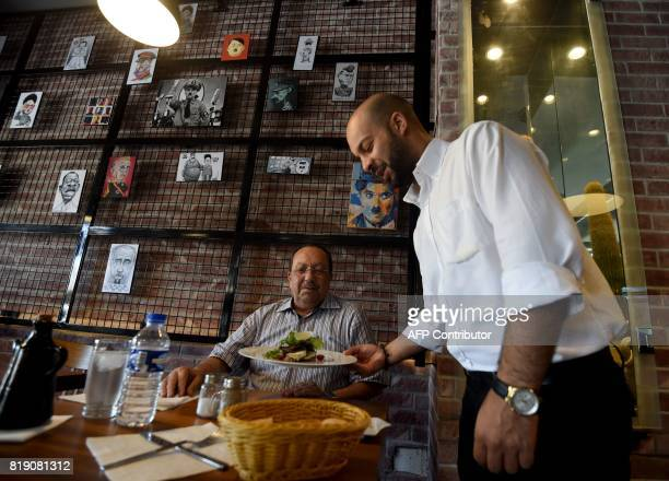 Cartoons adorn the walls of restaurant 'The Dictator' while a customer is served on July 5 2017 in the upmarket Cite Ennasr suburb of Tunis A steak...
