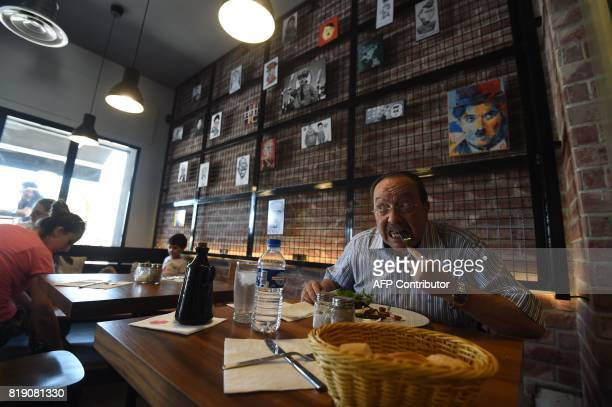 Cartoons adorn the walls of restaurant 'The Dictator' while a customer eats on July 5 2017 in the upmarket Cite Ennasr suburb of Tunis A steak named...
