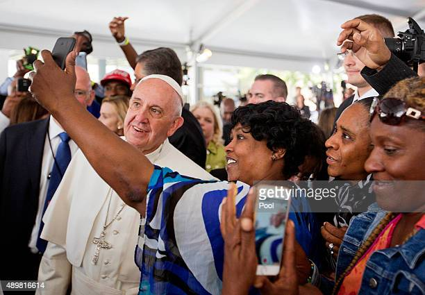 Cartrice Haynesworth center has a selfie taken with Pope Francis left as he walks through the crowd during a visit to Catholic Charities of the...