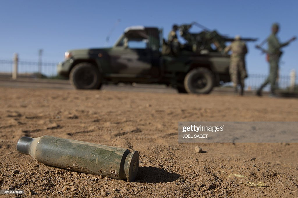 A cartridge is pictured on the floor next Malian soldiers walking near their armoured vehicle on February 22, 2013 in Gao, northern Mali. Five people, including two suicide bombers, died on February 22 in car bombings in northern Mali, a day after fierce urban battles between French-led forces and Islamists left up to 20 extremists dead, officials said. AFP PHOTO /JOEL SAGET