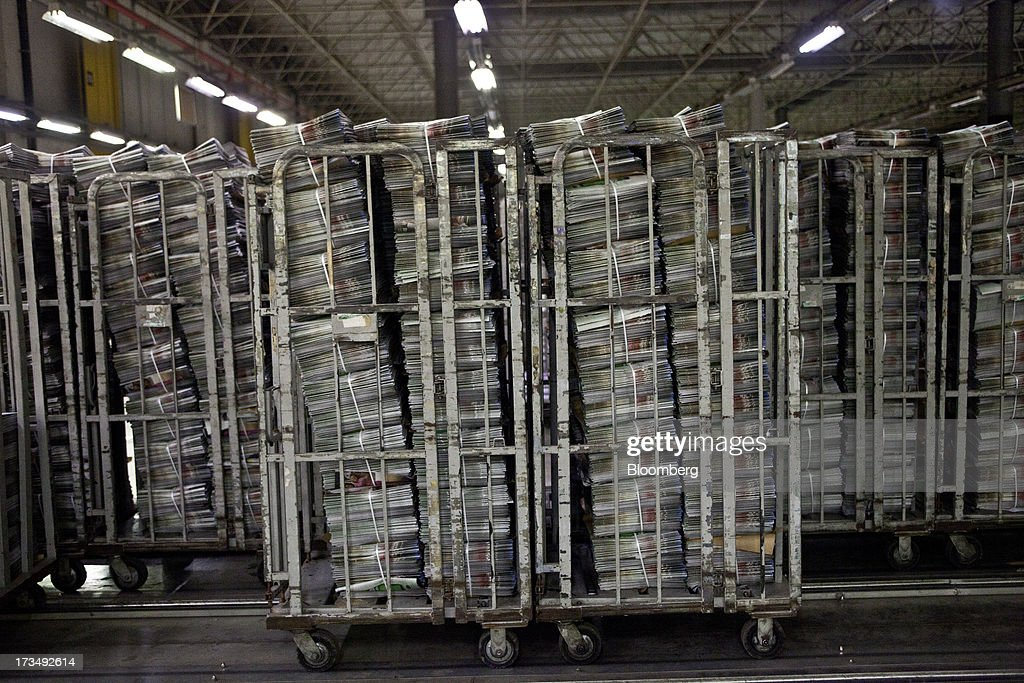 Carts full of newspapers wait to be delivered at the O Globo press park in Rio de Janeiro, Brazil, on Friday, July 12, 2013. Brazil economists raised their 2014 benchmark interest rate forecast to the highest all year, as policy makers work to slow inflation that has curbed consumption and confidence in the world's second-biggest emerging market. Photographer: Dado Galdieri/Bloomberg via Getty Images
