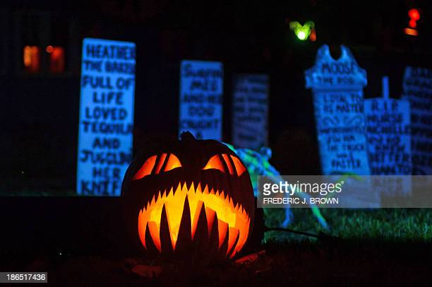 A carved and lit pumpkin is placed among what appears to be tombstones in a neighborhood decorated for Halloween in Sierra Madre California on...