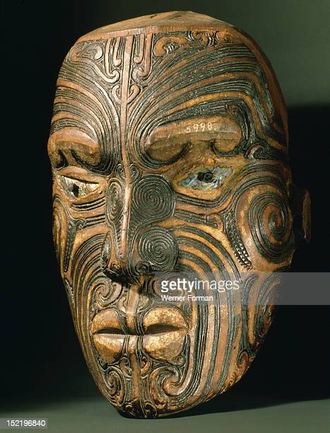 A carved wood Maori head with inlaid shell eyes It represents a specific ancestor who can be recognised by his distinctive pattern of moko facial...