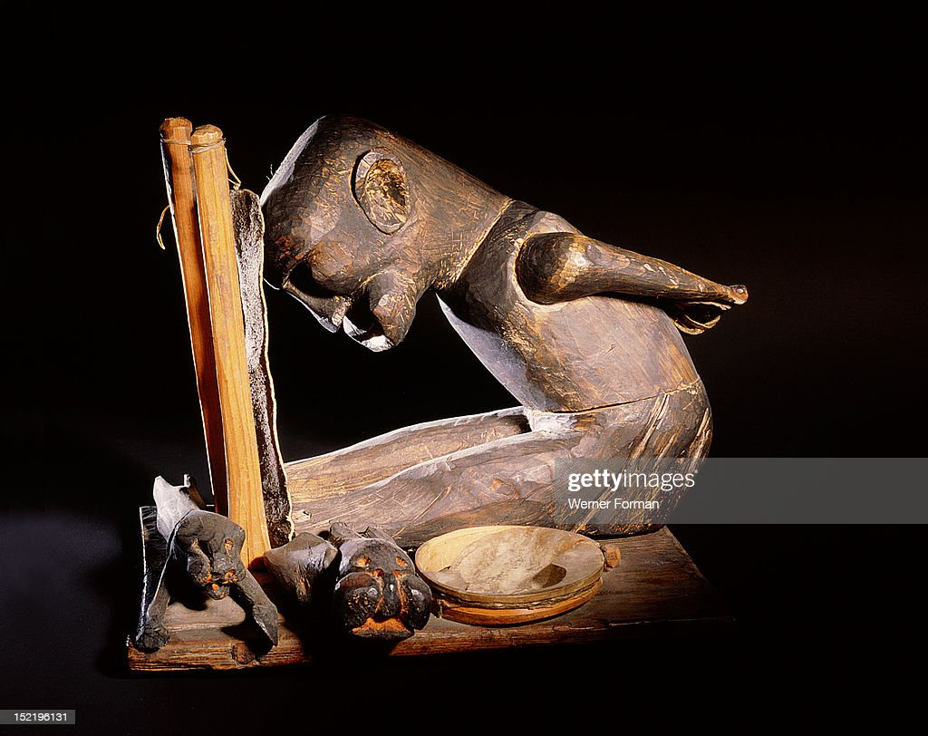 A carving representing a shaman in the middle of a seance and his two helping spirits in the form of animal like creatures A drum which was commonly...