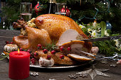 Carving rustic style roasted Christmas turkey garnished with roasted garlic, lemon, and rosehips. Surrounded with rustic Christmas ornaments, candles, wine, flowers, and Christmas tree in the backgrou