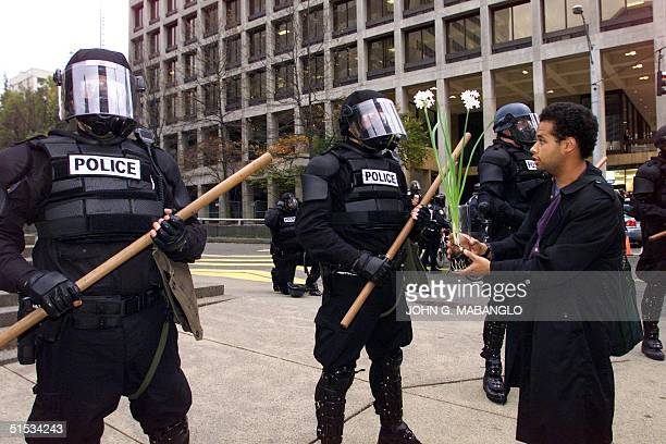 Carwil James of Berkeley California and member of Project Underground offers a flower to Seattle Riot Police near the Washington State Convention and...