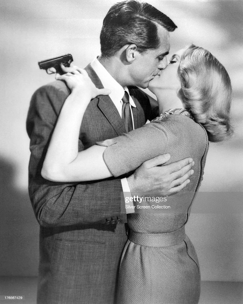Cary Grant (1904 - 1986) and Eva Marie Saint kissing in a publicity still for 'North By Northwest', directed by Alfred Hitchcock, 1959. Saint is holding a pistol.