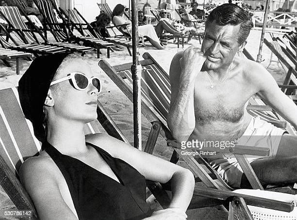 Cary Grant and Grace Kelly lounging on the beach in a scene from the 1955 classic To Catch a Thief