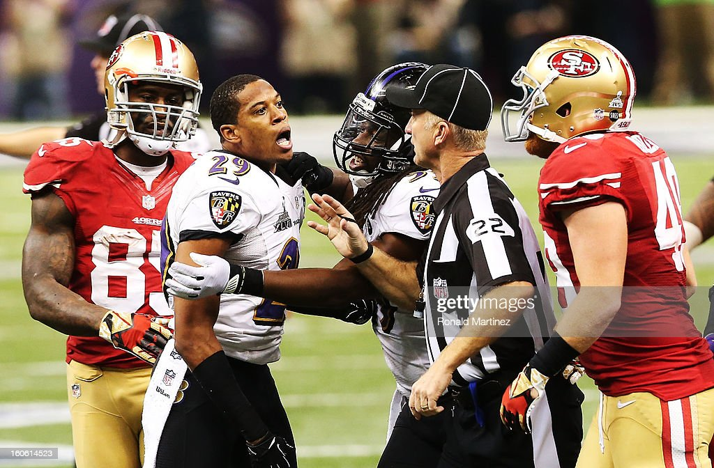 Cary Williams #29 of the Baltimore Ravens is held back by Dannell Ellerbe #59 and head linesman Steve Stelljes #22 from Bruce Miller #49 of the San Francisco 49ers during Super Bowl XLVII at the Mercedes-Benz Superdome on February 3, 2013 in New Orleans, Louisiana.