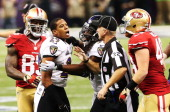 Cary Williams of the Baltimore Ravens is held back by Dannell Ellerbe and head linesman Steve Stelljes from Bruce Miller of the San Francisco 49ers...