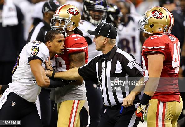 Cary Williams of the Baltimore Ravens reacts in front of head linesman Steve Stelljes and Bruce Miller of the San Francisco 49ers following personal...