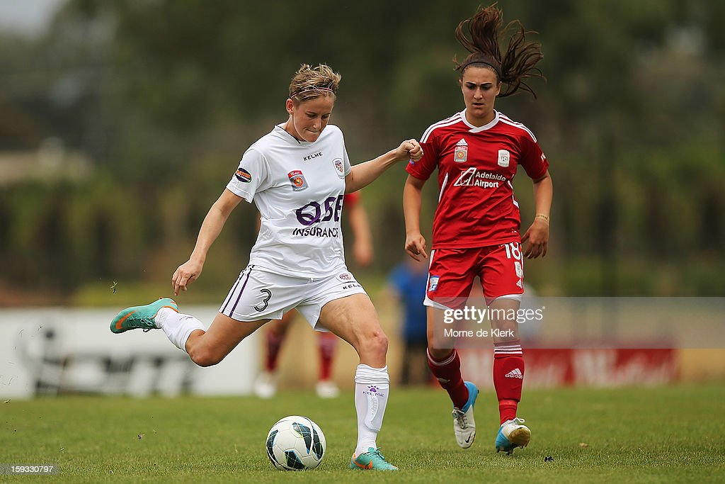 Carys Hawkins of Perth gets the ball away from Georgia Macri of Adelaide during the round 12 W-League match between Adelaide United and the Perth Glory at Burton Park on January 12, 2013 in Adelaide, Australia.