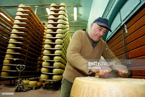 Casaro or cheesemaker Carlo Frandini cleans a wheel of ParmigianoReggiano or parmesan cheese that has completed its aging cycle in preparation for...