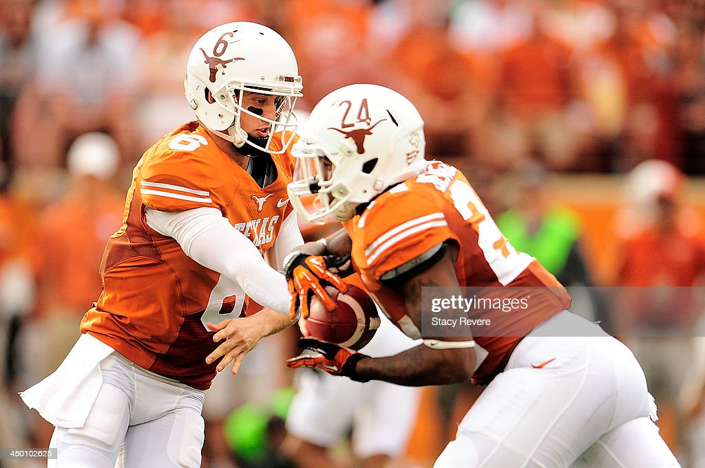 Case McCoy #6 hands the ball to Joe Bergeron #24 of the Texas Longhorns during a game against the Oklahoma State Cowboys at Darrell K Royal-Texas Memorial Stadium on November 16, 2013 in Austin, Texas. Oklahoma State won the game 38-13.