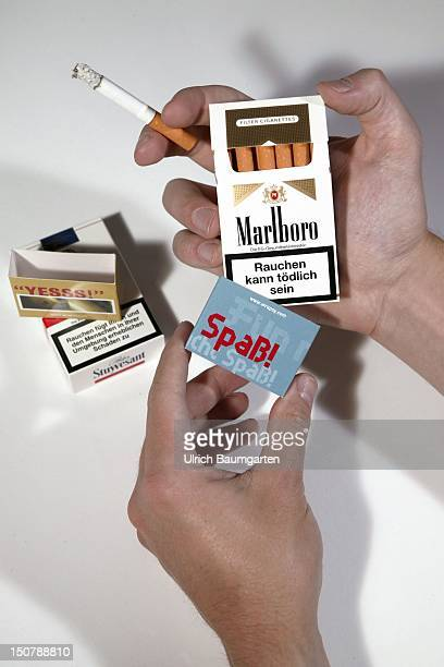 Case with the writing 'Spass' for covering the big warning signs about the health risks from smoking on the cigarette boxes A hand is putting a case...