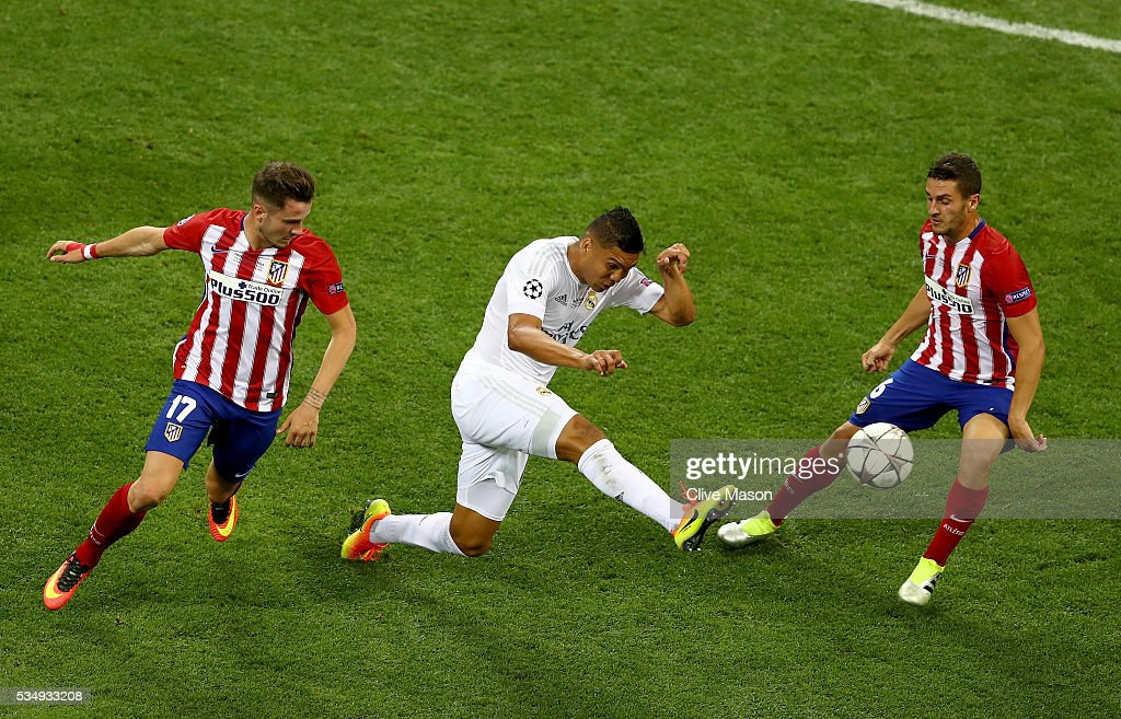 <a gi-track='captionPersonalityLinkClicked' href=/galleries/search?phrase=Casemiro&family=editorial&specificpeople=7150894 ng-click='$event.stopPropagation()'>Casemiro</a> of Real Madrid clears the ball from Saúl Níguez of Atletico Madrid and <a gi-track='captionPersonalityLinkClicked' href=/galleries/search?phrase=Koke+-+Soccer+Midfielder+-+Born+1992&family=editorial&specificpeople=11132098 ng-click='$event.stopPropagation()'>Koke</a> of Atletico Madrid during the UEFA Champions League Final match between Real Madrid and Club Atletico de Madrid at Stadio Giuseppe Meazza on May 28, 2016 in Milan, Italy.