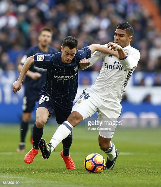 Casemiro of Real Madrid competes for the ball with Juanpi of Malaga during the La Liga match between Real Madrid and Malaga CF at Estadio Santiago...