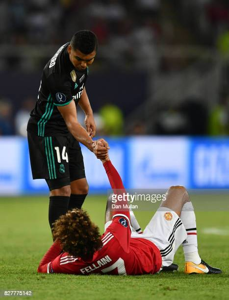Casemiro of Real Madrid helps Marouane Fellaini of Manchester United up after the UEFA Super Cup final between Real Madrid and Manchester United at...