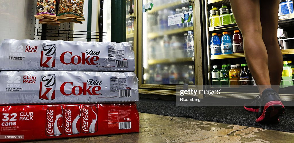 Cases of Coca-Cola Co. and Diet Coke soda are displayed for sale as a customer browses refrigerated beverages at a convenience store in Redondo Beach, California, U.S., on Monday, July 15, 2013. The Coca-Cola Co. is scheduled to release earnings data on July 16. Photographer: Patrick Fallon/Bloomberg via Getty Images