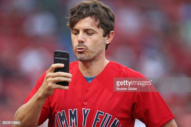 Casey Affleck records a short video on the phone of a fan before throwing out the ceremonial first pitch before the game as part of the 16th Annual...