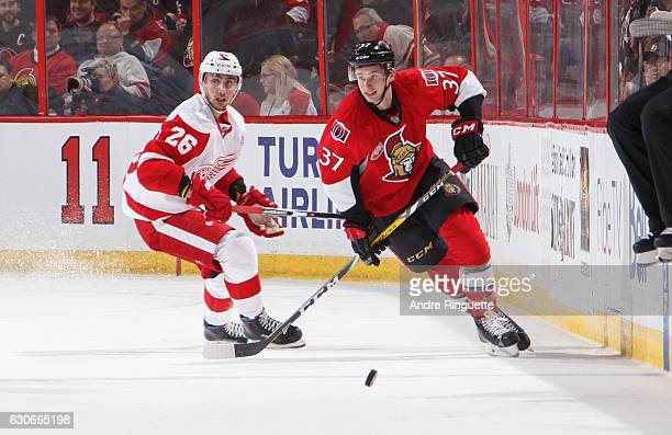 Casey Bailey of the Ottawa Senators chases a loose puck against Tomas Jurco of the Detroit Red Wings at Canadian Tire Centre on December 29 2016 in...