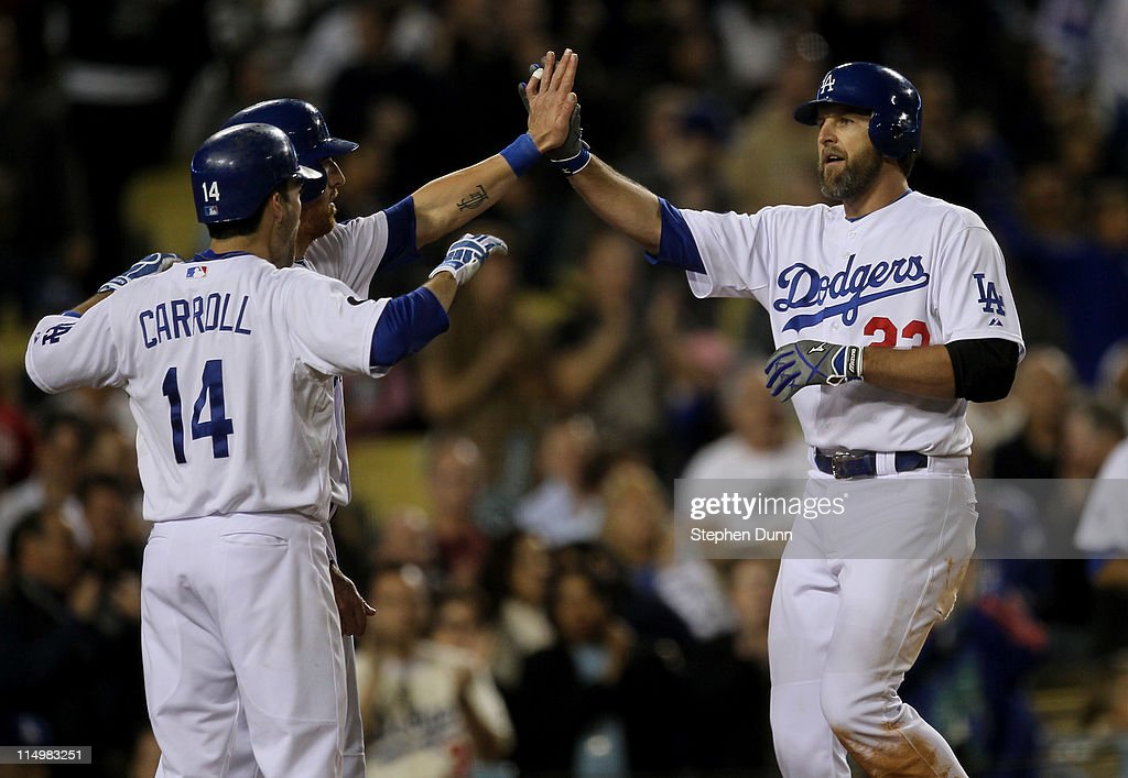 Casey Blake #23 of the Los Angeles Dodgers is greeted by Jay Gibbons #31 and Jamey Carroll #14 as all three score on Blake's three run home run in the seventh inning against the Colorado Rockies on May 31, 2011 at Dodger Stadium in Los Angeles, California.